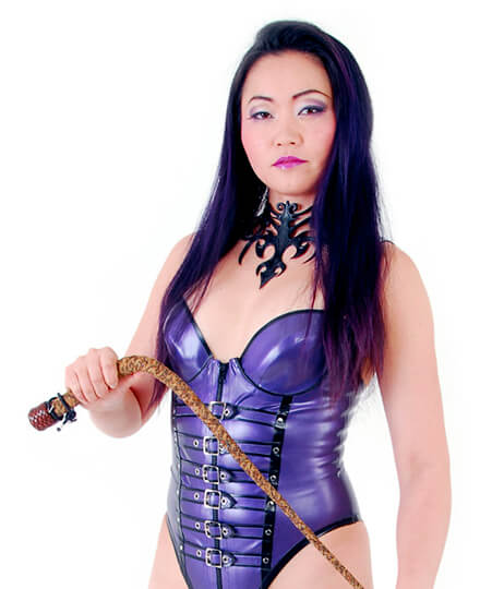 Mistress Amrita holding a whip and wearing purple latex fetish dress